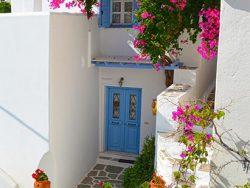 Tuinposter Grieks huis met blauwe deur en bougainville